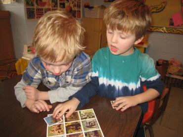 Dos chicos aprendiendo los nombres de los animales (Two boys learning animal names).